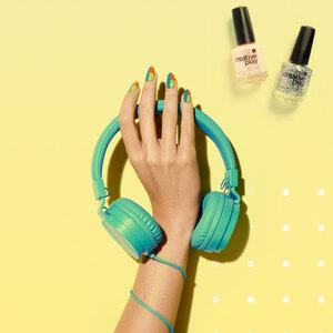 Hand met gelakte nagels die groene koptelefoon omhoog houdt
