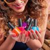 Vrouw die een hoop nagellak flesjes in de handen heeft
