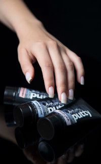 Hand boven enkele tubes Artistic Polygel Putty voor een zwarte achtergrond