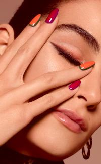 Vrouw die hand met gelakte nagels voor aangezicht houdt