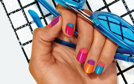 Hand met zonnebril en gekleurde nagels